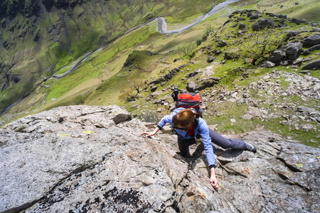 scrambling: Una femmina di scalatore arrampicandosi Cam Ridge in Langstrath valle che porta alla vetta del Glaramara nel Lake District. Archivio Fotografico