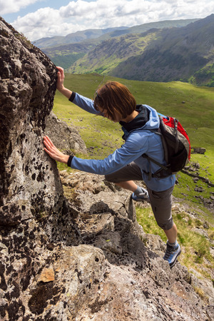 scrambling: A climber scrambling up Gillercombe Crag (Rabbits Trod scramble) on Grey Knotts in the Lake District, UK.