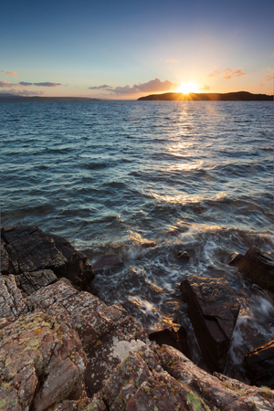 isles: Sun setting behind Horse Island near the Summer Isles in the Highlands of Scotland. Stock Photo