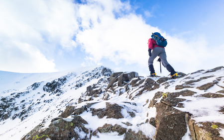 crampons: Climber ascending a snow covered ridge in the Lake District UK. Swirral Edge on Helvellyn.