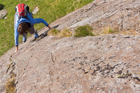 scrambling: Female rock scrambler climbing up Seathwaite Slabs, Lake District, UK.
