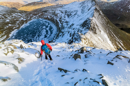 A hiker descending Helvellyn towards Striding Edge and Red Tarn in the Lake District, UK.