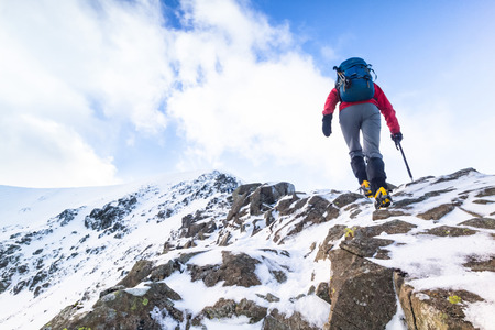 ascending: Climber ascending a snow covered ridge in the Lake District UK. Swirral Edge on Helvellyn.