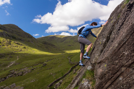 scrambler: Female rock scrambler climbing up Seathwaite Slabs, Lake District, UK.