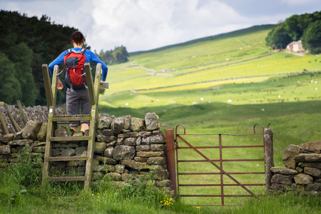 stile: A hiker crossing a stile on the Hadrians Wall Walk in Northumberland, North East of England, UK. Stock Photo