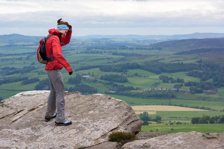 gust: A hiker at Simonside Hills near Rothbury on a windy day, Northumberland, England, UK.