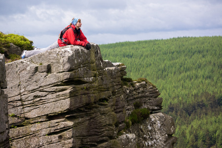 the crags: A hiker taking in the views from Simonside Crags near Rothbury, Northumberland, England, UK. Stock Photo