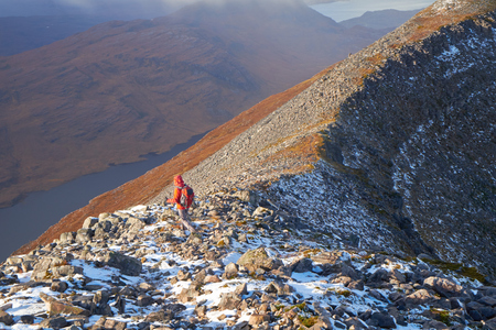 toll: A hiker walking towards Toll nam Biast on Beinn Damh in the Scottish Highlands, UK.