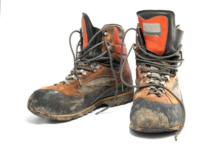 muddy clothes: A pair worn hiking boots isolated on a white .