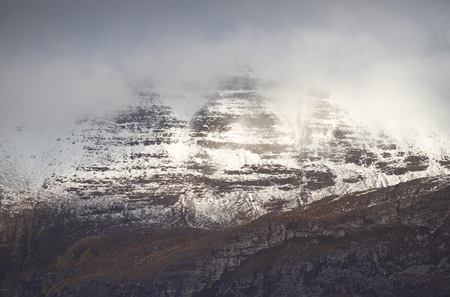 cloud capped: A cloud and snow capped summit of Beinn a Mhuinidh in the Scottish Highlands.