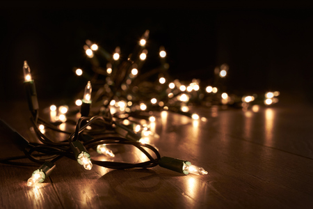 Traditional Christmas Tree lights lying on a wooden floor.