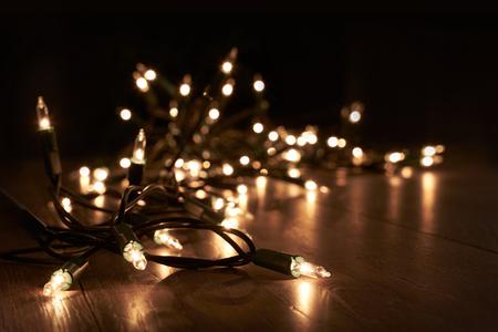 Traditionele kerst boom lichten liggend op een houten vloer.