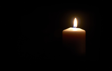 Lit white candle on a dark  black background.