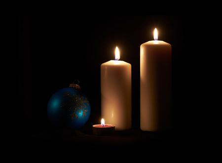 candela: Lit candele bianche e pallina su un pavimento di legno scuro con sfondo nero.