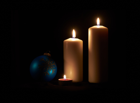 candles: Lit white candles and bauble on a dark wooden floor with black background.