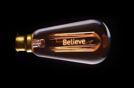 creer: Religión, creen concepto en una bombilla de filamento. Foto de archivo