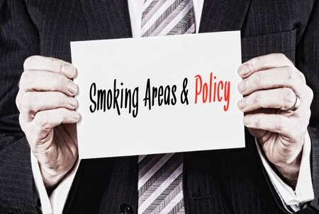 areas: Smoking Areas & Policy, Induction Training headlines concept hold by businessman hands Stock Photo