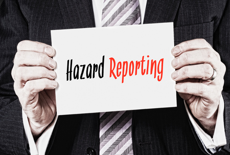 reporting: Hazard Reporting, Induction Training headlines concept hold by businessman hands