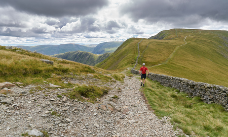 A man fell running down from The Knott and on towards the summit of High Street in the English Lake District, UK.
