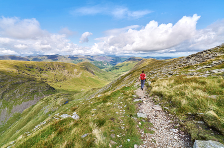 beck: A hiker walking down from the summit of High Street, over Thornthwaite Crag and towards Pasture Beck in the English Lake District, UK.