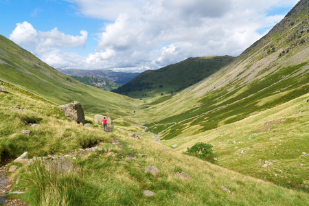 the crags: A female hiker walking towards Hartsop and Brock Crags  in the English Lake District, UK.