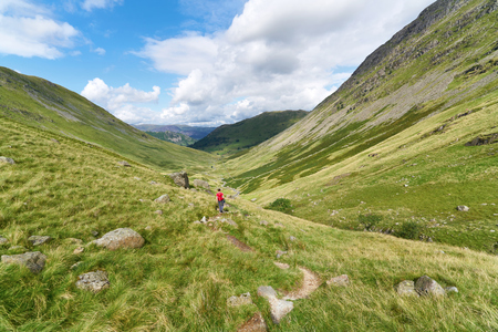 valley view: A female hiker walking towards Hartsop and Brock Crags  in the English Lake District, UK.