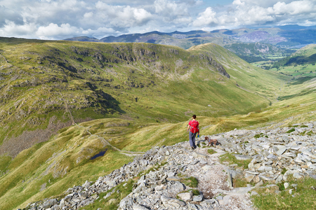 crag: A hiker walking down from the summit of High Street, over Thornthwaite Crag and towards Pasture Beck in the English Lake District, UK.