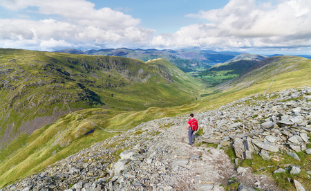 the crag: A hiker walking down from the summit of High Street, over Thornthwaite Crag and towards Pasture Beck in the English Lake District, UK.