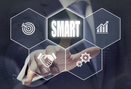 acronym: Businessman pressing a SMART acronym concept button.