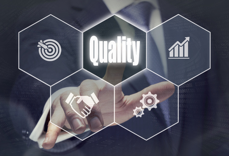 Businessman pressing a Quality concept button. Standard-Bild