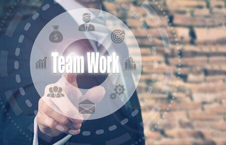 synergism: Businessman pressing an Teamwork concept button. Stock Photo