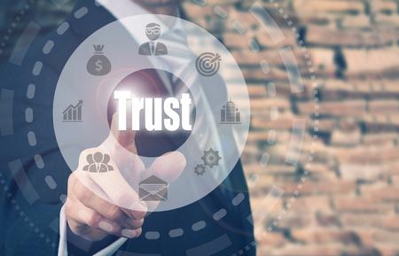 definition define: Businessman pressing an Trust concept button.