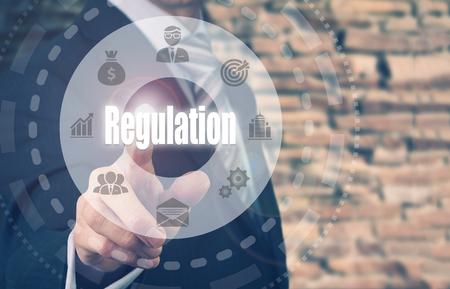 regulated: Businessman pressing an Regulation concept button. Stock Photo
