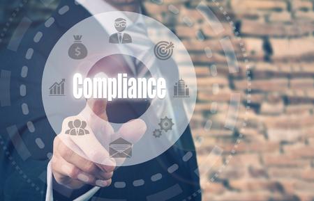 Businessman pressing an Compliance concept button.