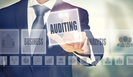 oversight: Businessman pressing an Auditing concept button. Stock Photo