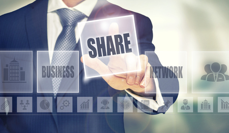 technology agreement: Businessman pressing an Sharing concept button. Stock Photo