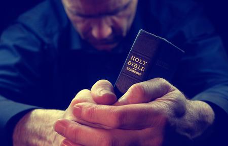 hombre orando: Un hombre rezando la celebraci�n de una Santa Biblia. Foto de archivo