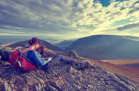 A hiker and their dog resting on a mountain summit. This image has added grain and styling.