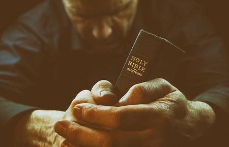 Un homme de prière tenue d'une Sainte Bible. Banque d'images