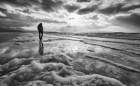 walking away: A woman walking alone on the beach. This image has added grain and styling. Stock Photo