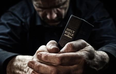 biblia: Un hombre rezando la celebración de una Santa Biblia. Foto de archivo