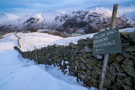 hause: Signpost by a stone wall pointing towards Bridgend, Patterdal in the English Lake District. Stock Photo