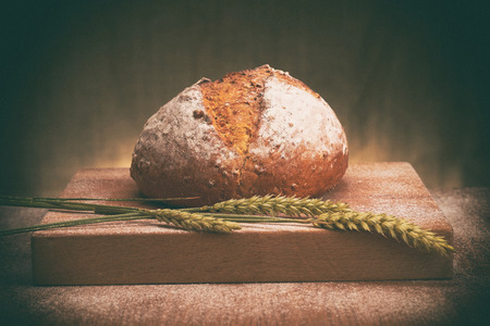 epicure: Freshly baked bread on a bread board. The image has added grain and styling.