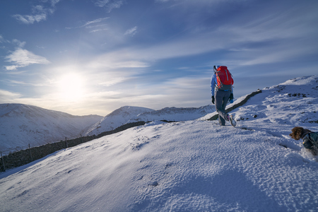 the crag: Hiker walking through the snow along Hartsop Above How that leads towards Hart Crag. English Lake District. Stock Photo