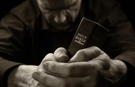 hombre orando: Un hombre rezando la celebración de una Santa Biblia. Foto de archivo