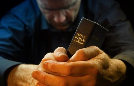 manos orando: Un hombre rezando la celebración de una Santa Biblia. Foto de archivo