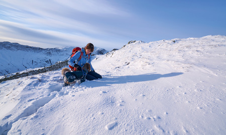 freshly fallen snow: Hiker checking their dog while walking in freshly fallen snow. Hartsop Above How in the Lake District.
