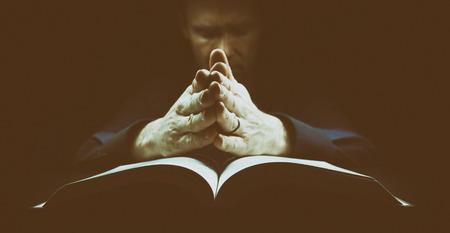 personas orando: El hombre orando con las manos apoyadas en la Biblia. La imagen tiene el grano agregado intencional y peinado.