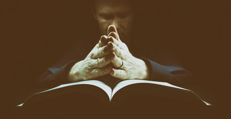 Man praying with his hands resting on the bible. The image has intentional added grain and styling.