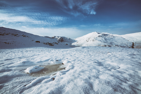 snow covered mountains: Views of snow covered mountains in the English countryside. Grain and styling applied.